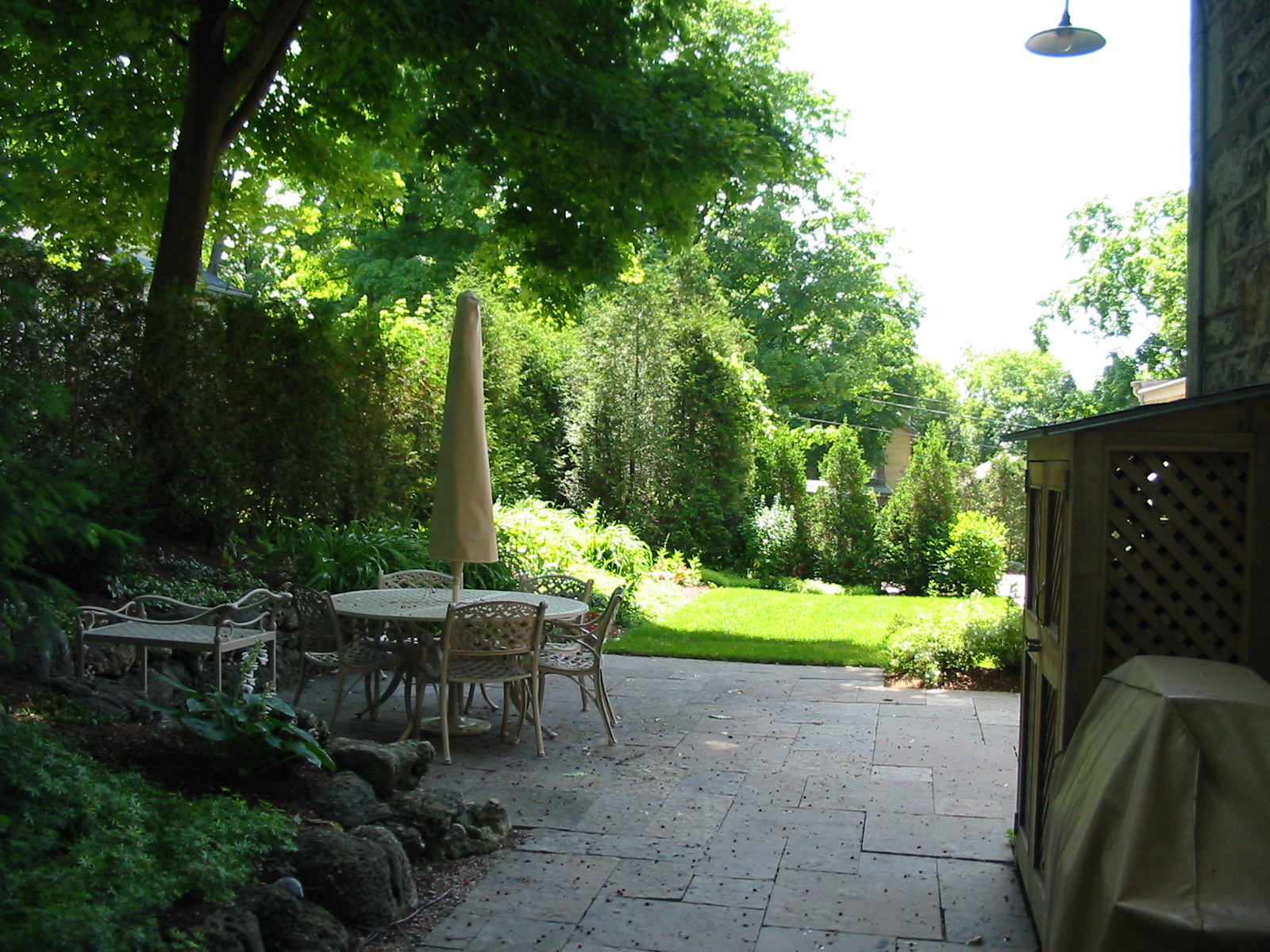 A shady patio surfaced with square cut natural stone