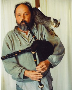 Robin Aggus playing small bagpipes, with a cat sitting on his shoulder.